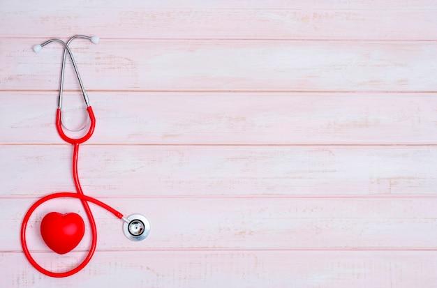 Stetoscopio e cuore rosso su legno rosa