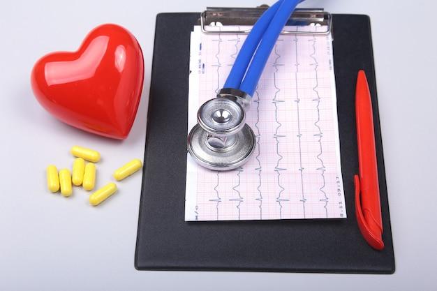 Stetoscopio, cuore rosso, prescrizione rx e pillole assortite sul tavolo bianco con spazio per il testo.