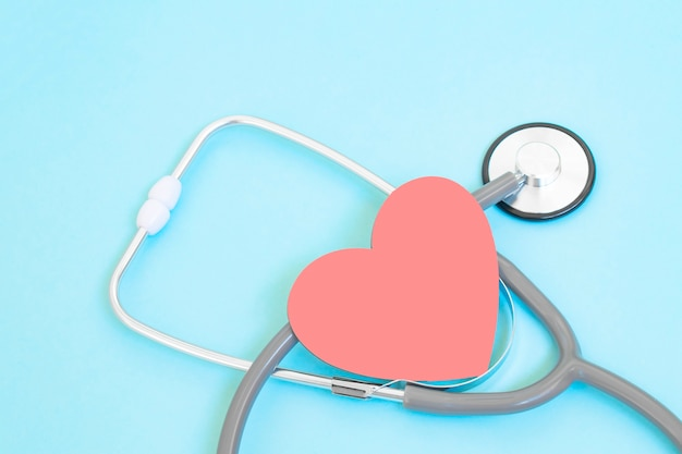 Stetoscopio e forma di cuore rosso su sfondo blu, cuore e concetto di assistenza sanitaria