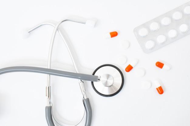 Stetoscopio, foglio di carta cuore rosso per le note su uno sfondo bianco sul tavolo