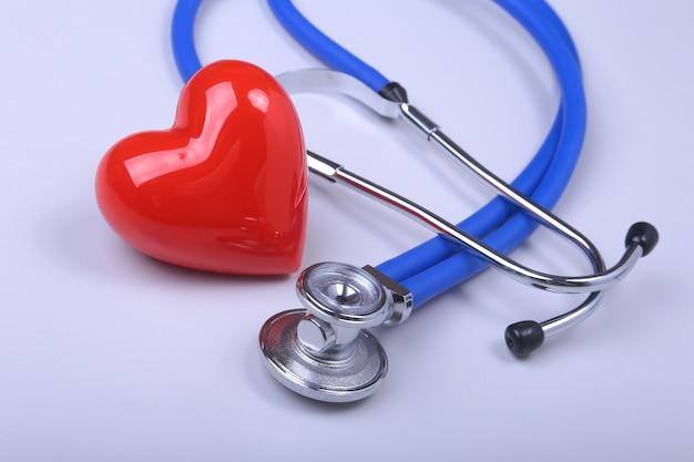 Stetoscopio e cuore rosso sul tavolo bianco con spazio per il testo.