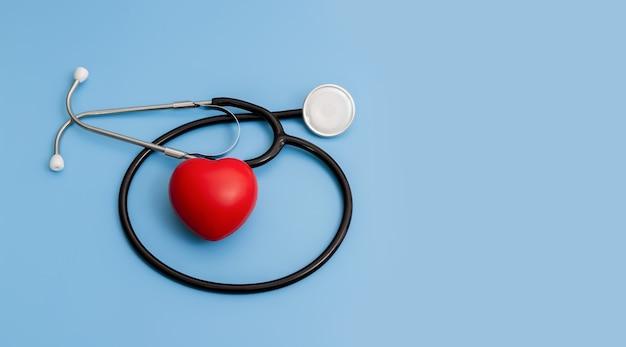 Stetoscopio e cuori rossi su sfondo blu concetto di assistenza sanitaria.