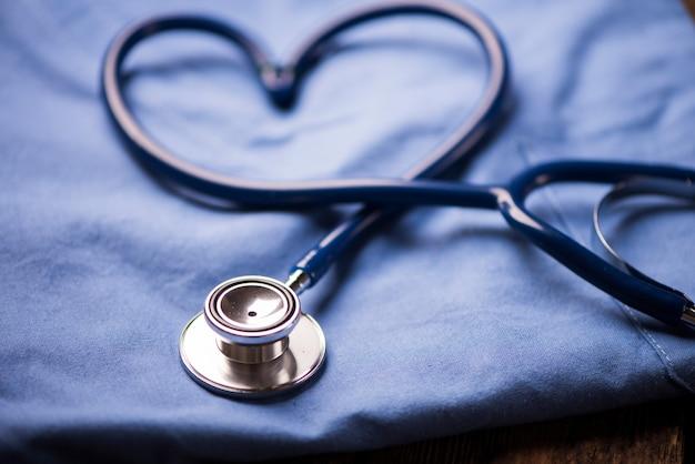 Uno stetoscopio che modella un cuore su un'uniforme medica, primo piano