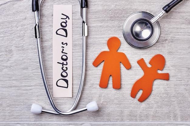 Stetoscopio, stickmen su fondo di legno. saluto del giorno del dottore.