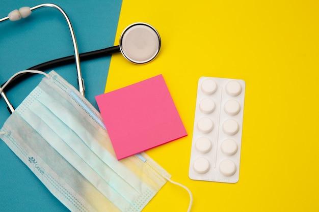Stetoscopio, compresse e nota adesiva rosa per il testo sopra la maschera per il viso su colorato.
