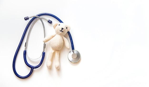Stetoscopio e orsacchiotto isolare su uno sfondo bianco. messa a fuoco selettiva.