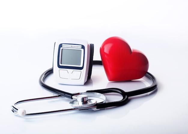 Stetoscopio, tonometro e cuore su sfondo bianco