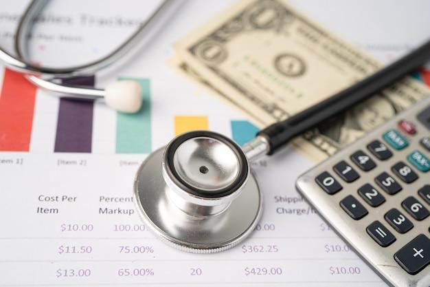 Stetoscopio e banconote in dollari usa su carta millimetrata.