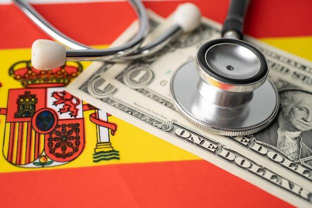 Stetoscopio e banconote in dollari usa sulla bandiera della spagna.