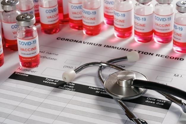 Bottiglie di vetro della fiala di vaccino e dello stetoscopio su fondo per la vaccinazione