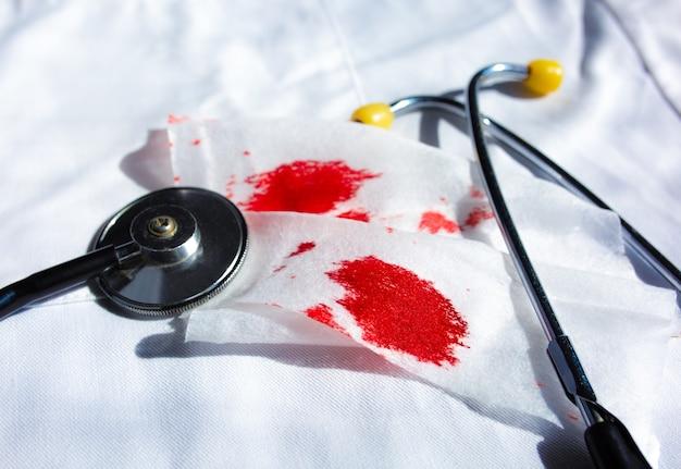 Stetoscopio e tovagliolo bianco con coaguli di macchie di sangue. casi pericolosi di ceppo influenzale. malattia epidemica. problema di virus. malattia polmonare e bronchite. effetto tosse.