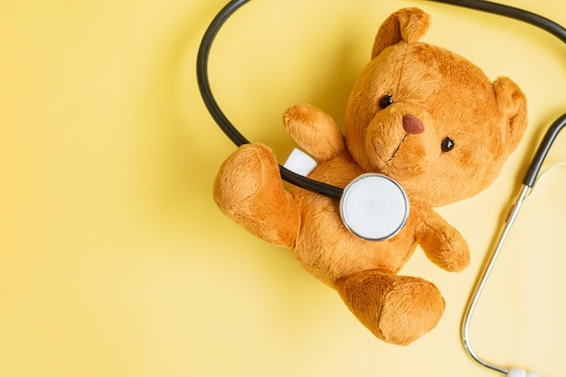 Stetoscopio con bambola orso su sfondo giallo per sostenere la vita e la malattia dei bambini. settembre childhood cancer awareness month, concetto di assicurazione sanitaria e sulla vita