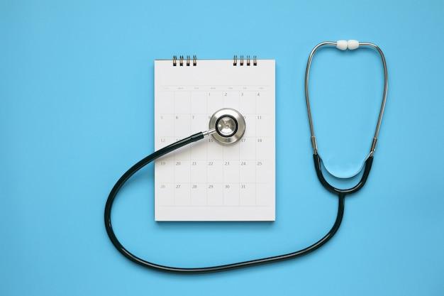 Stetoscopio con data di pagina del calendario sul tavolo blu, concetto medico appuntamento medico