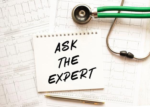 Stetoscopio con cardiogramma e blocco note con testo chiedere all'esperto. concetto medico.