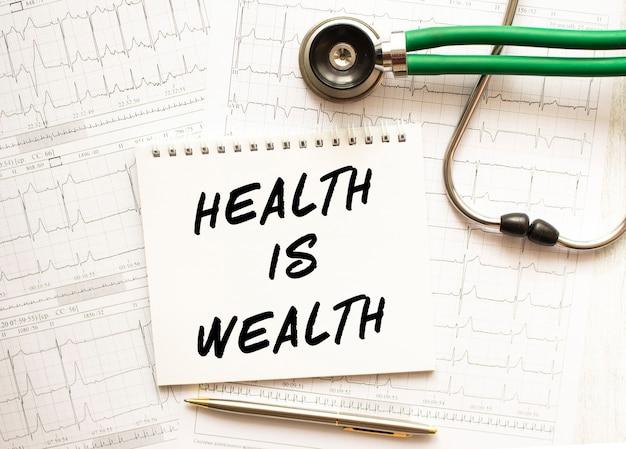 Stetoscopio con cardiogramma e blocco note con testo la salute è ricchezza. concetto di assistenza sanitaria.