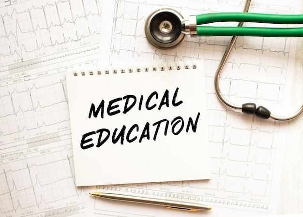 Stetoscopio con cardiogramma e blocco note con testo formazione medica. concetto di assistenza sanitaria.