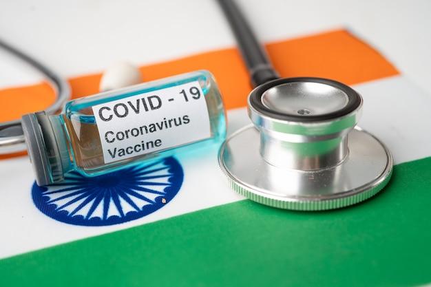 Stetoscopio con vaccino contro il coronavirus covid-19 sulla bandiera dell'india.