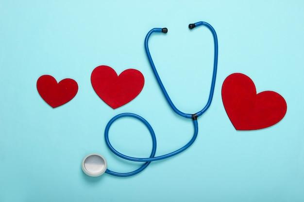 Stetoscopio con cuori su un pastello blu