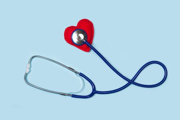 Uno stetoscopio con un cuore rosso su sfondo azzurro in una vista dall'alto