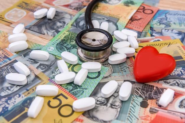 Stetoscopio con cuore rosso e pillole su dollari australiani