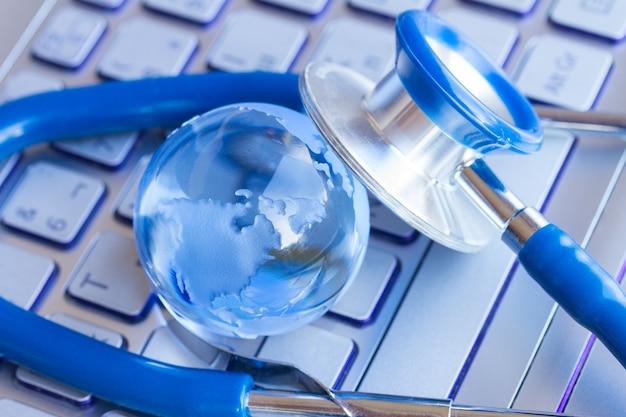 Stetoscopio e globo di vetro sul concetto di assistenza sanitaria e ambiente della tastiera del computer portatile