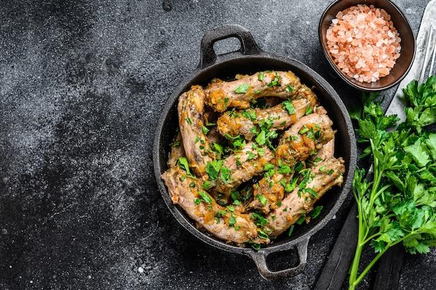 Spezzatino con carne di collo di pollo e verdure. sfondo nero. vista dall'alto.
