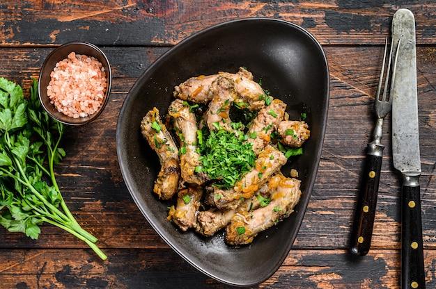 Spezzatino con carne di collo di pollo e verdure. fondo in legno scuro. vista dall'alto.