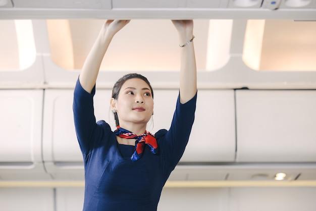 La hostess aiuta i passeggeri a mettere i bagagli nella cabina dell'aereo. hostess in aereo.