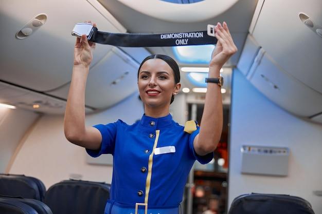 L'hostess mostra le regole di sicurezza prima di volare al salone dell'aereo serale