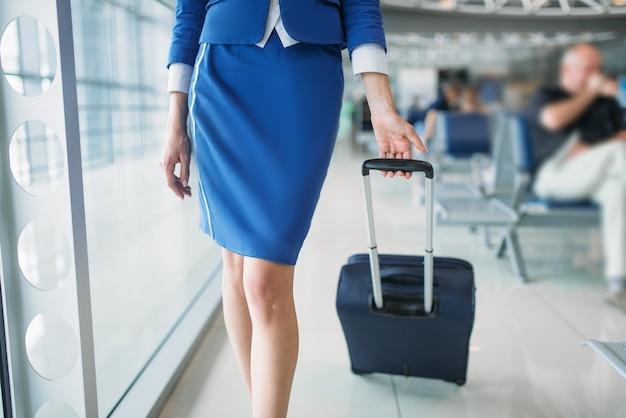 Hostess gambe e valigia nella hall dell'aeroporto