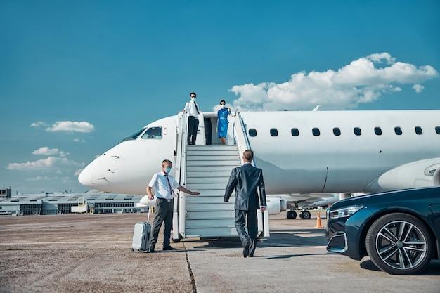 Hostess e pilota stanno incontrando un uomo elegante con una guardia del corpo che trasporta la valigia mentre tutti indossano maschere