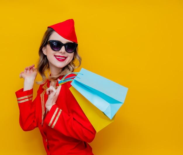 Hostess che indossa in uniforme rossa con borse della spesa. Foto Premium