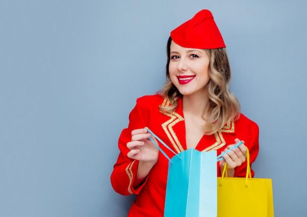 Hostess che indossa in uniforme rossa con borse della spesa.