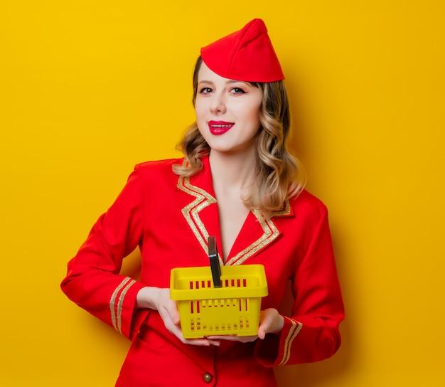 Hostess che indossa in uniforme rossa con carrello della spesa