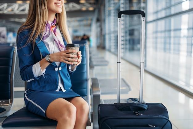 Hostess con caffè sul sedile in sala d'attesa