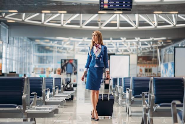Hostess con bagaglio a mano andando nella hall dell'aeroporto