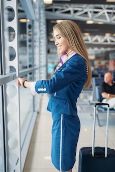 Hostess con la valigia contro la finestra in aeroporto