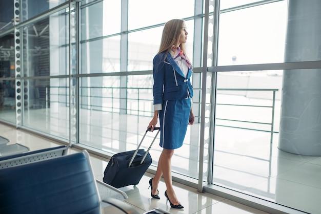 Hostess con la valigia in sala d'attesa dell'aeroporto