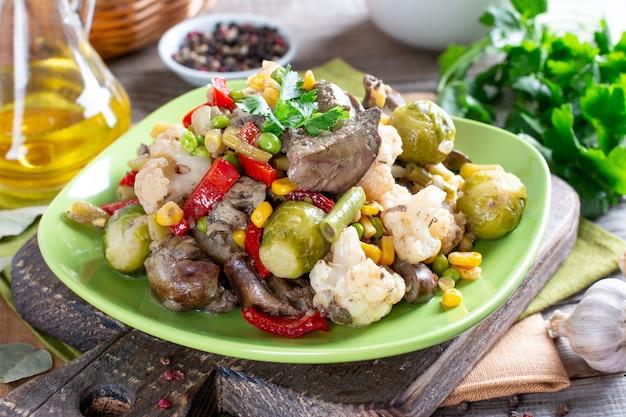 Verdure stufate con fegato di pollo sul tavolo di legno. cibo salutare.