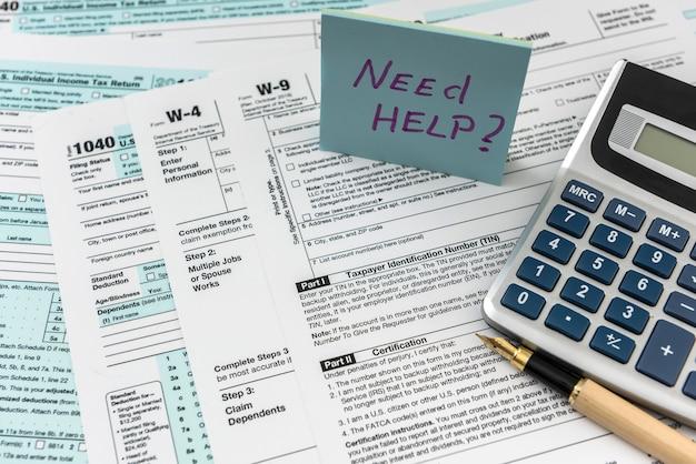 Adesivo con testo serve aiuto e modulo fiscale 1040, penna e calcolatrice