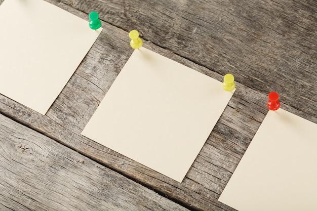 Note adesive con spilli in fila su una superficie di legno
