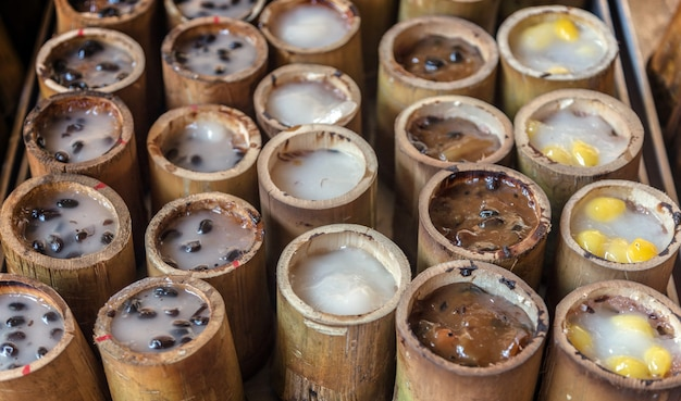 Il riso stiky e il latte di cocco condizionato e i fagioli del dessert tailandese servono sul taglio del legno di bambù