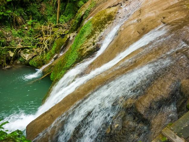 Ancora bello, anche con flusso ridotto all'inizio dell'autunno, si riversa e precipita su una scogliera calcarea muschiosa. cascata