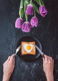 Ancora colazione per una persona cara con i tulipani su uno sfondo scuro