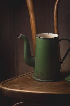 Natura morta del bollitore verde antico sulla sedia su vintage