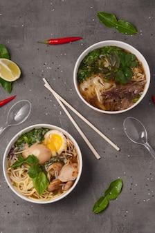 Una natura morta di zuppe di ramen asiatiche e una foto su sfondo grigio in piatti artigianali. concetto: consegna di cibo, cibo di strada