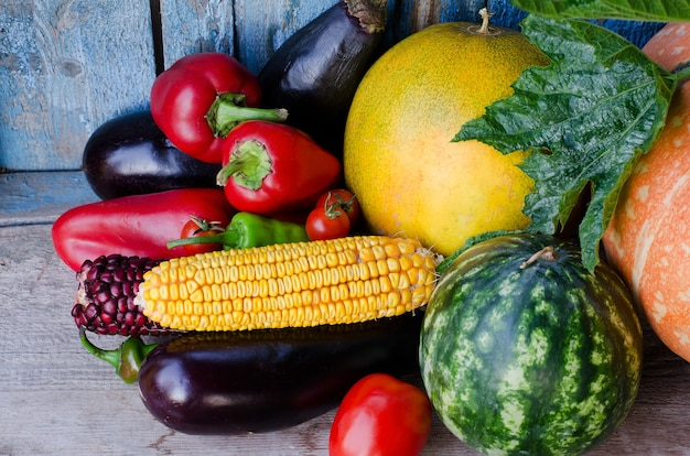 Natura morta di verdure autunnali: melone, anguria, mais, melanzane, peperoni, pomodori