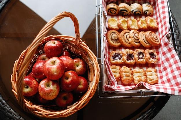 Natura morta. cestino con mele rosse e muffin su un asciugamano a scacchi. vista dall'alto.