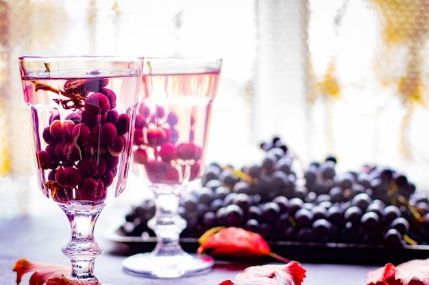 Natura morta di uva blu e una bevanda rinfrescante