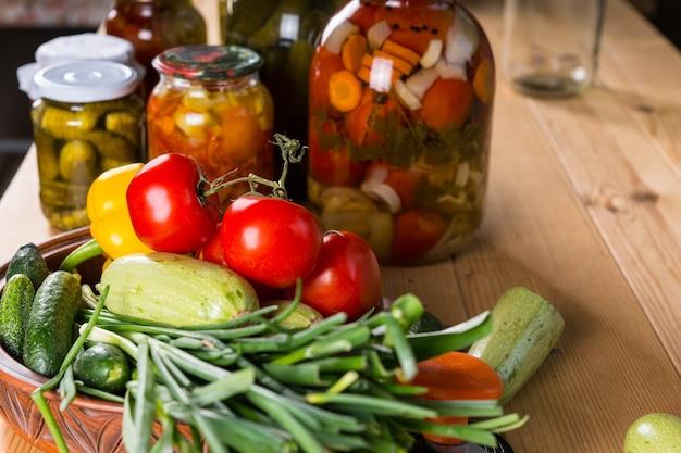 Natura morta di abbondanza di verdure fresche e vasetti di sottaceti su tavola di legno